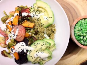 Quinoa bowl with roasted veggies, avocado, and garlic aioli