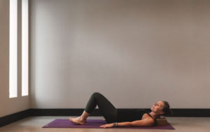 woman Laying on yoga mat doing yoga - Kind Living - Orillia
