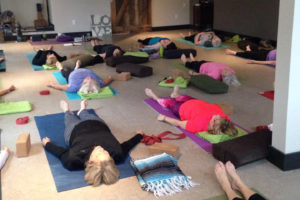 Women participating in a Yoga class, laying down in Savasana